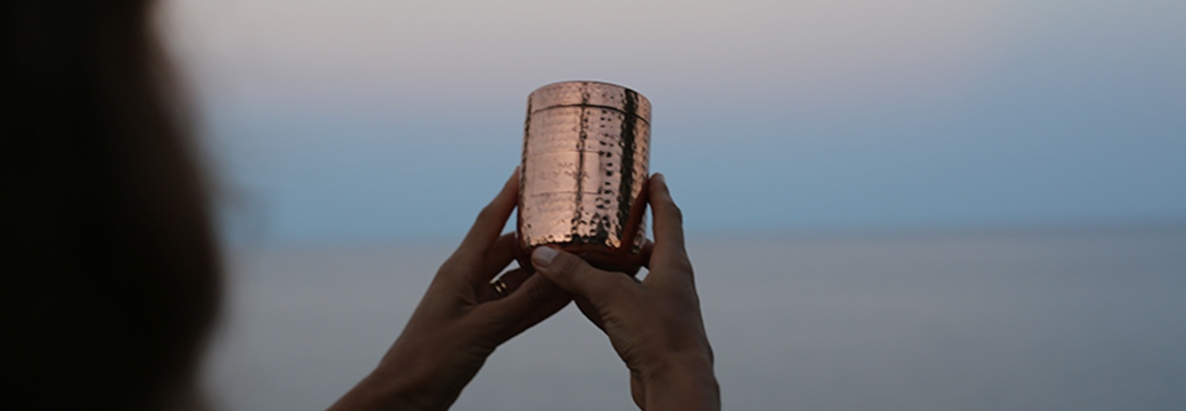 TWO HANDS HOLDING VESSEL
