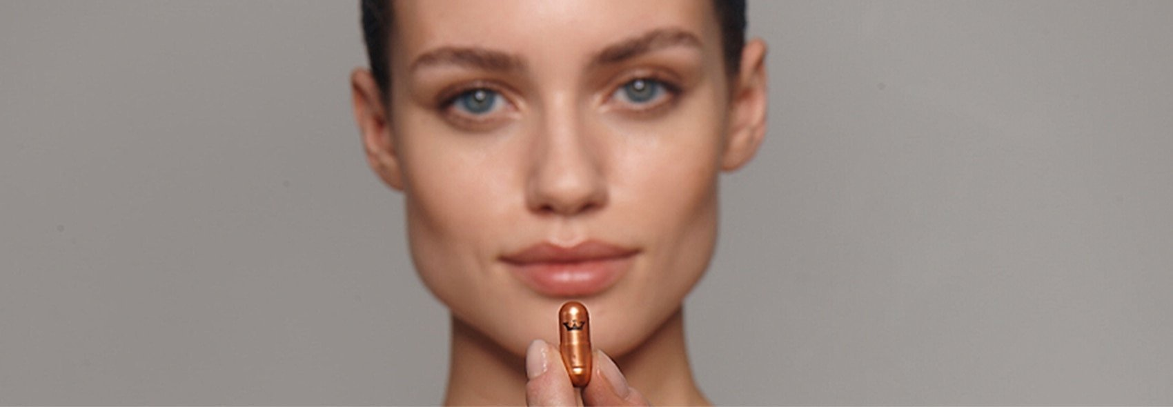 woman with vitamin pill next to chin